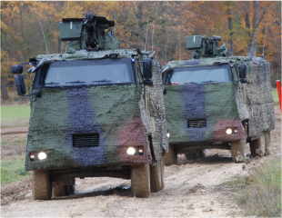 Two APCs fitted with camouflage kits underway at the Bure training ground