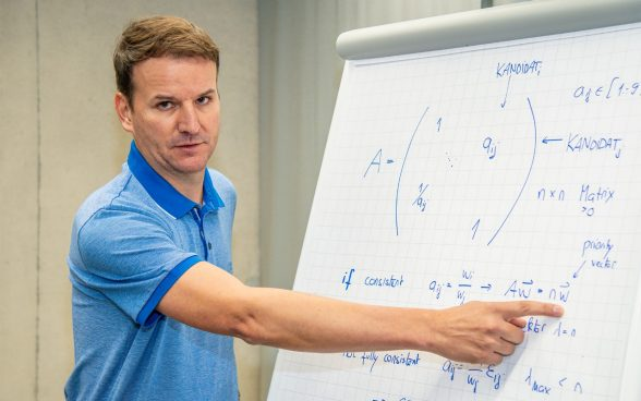 Xavier Comby stands in front of a flipchart and explains an equation