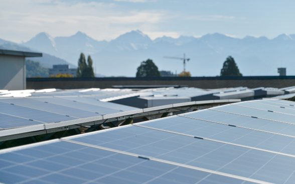 Photovoltaic systems decorate the roof of the Chaufferie Sud in Payerne, with a crane, trees and the Alps in the background.
